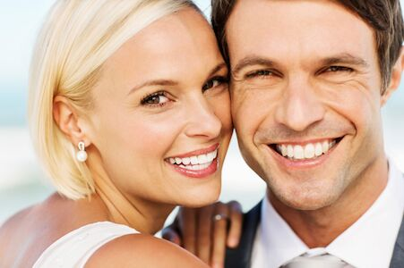 Young couple showing off how much teeth whitening improved the look of their smile for their wedding.