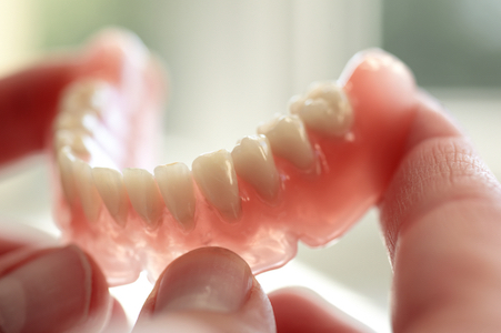 Closeup of a hand holding the bottom tray of dentures that can be made at Boca Smile Center in Boca Raton, FL.
