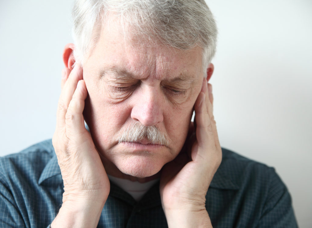 Man with ear pain which is symptom of possible TMJ.