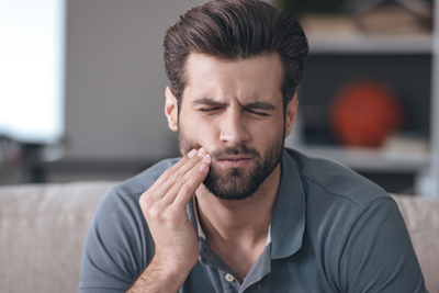 man wincing in pain from a toothache and needing an emergency dentist visit for help.