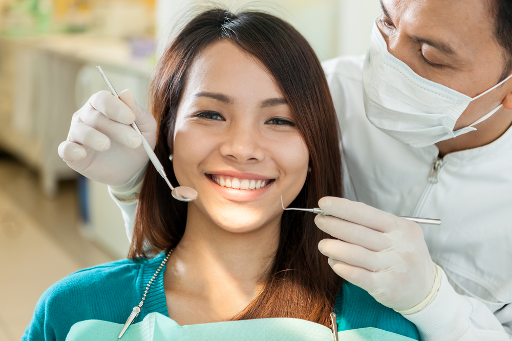 Woman getting an exam by a periodontist who is screening her for gum disease.